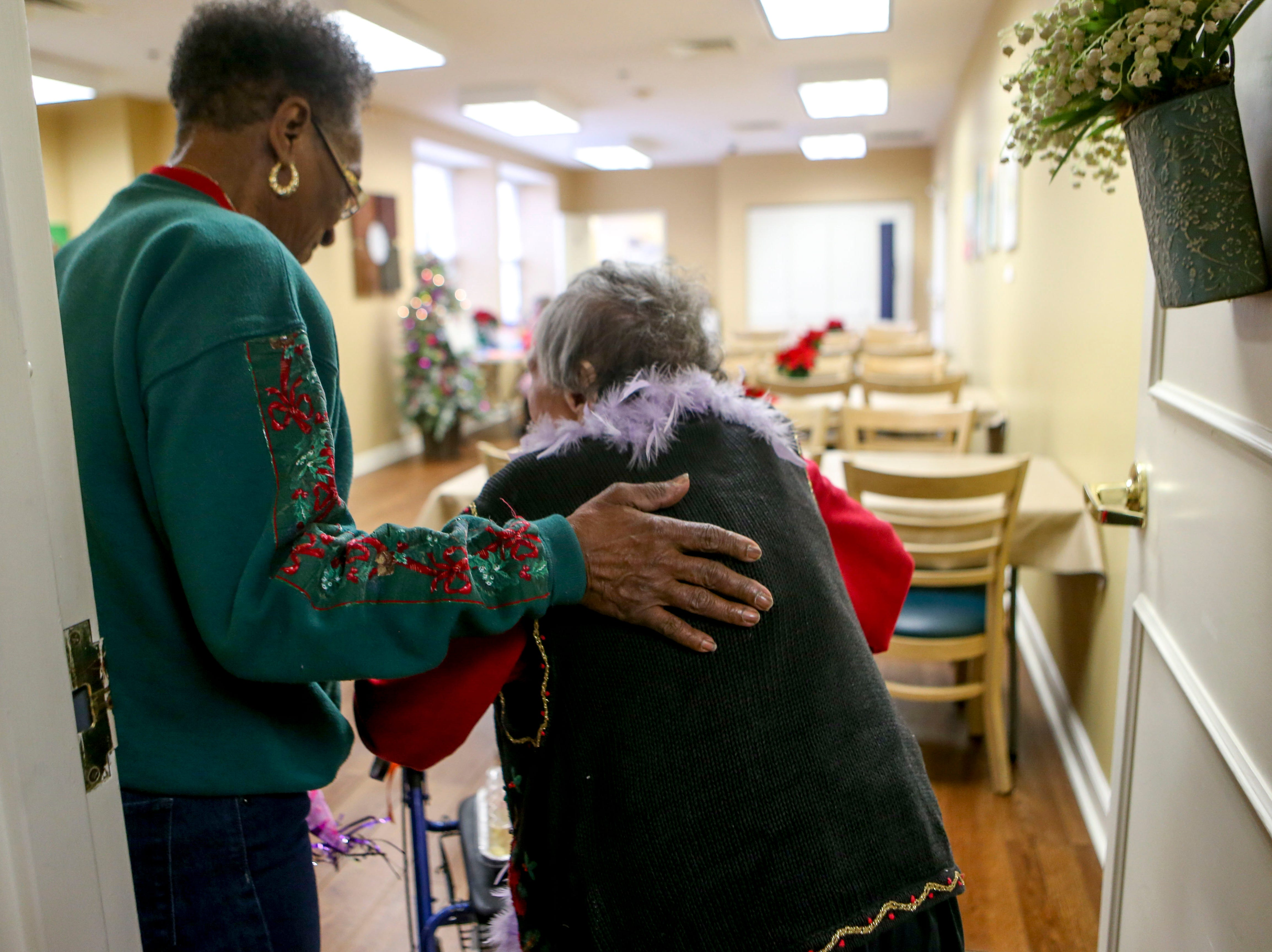 Anne Boston guides Ida Feldman, who turned 100 years old on Thursday, into the cafeteria for photos on her birthday at Regency Retirement Home in Jackson, Tenn., on Thursday, Dec. 20, 2018.