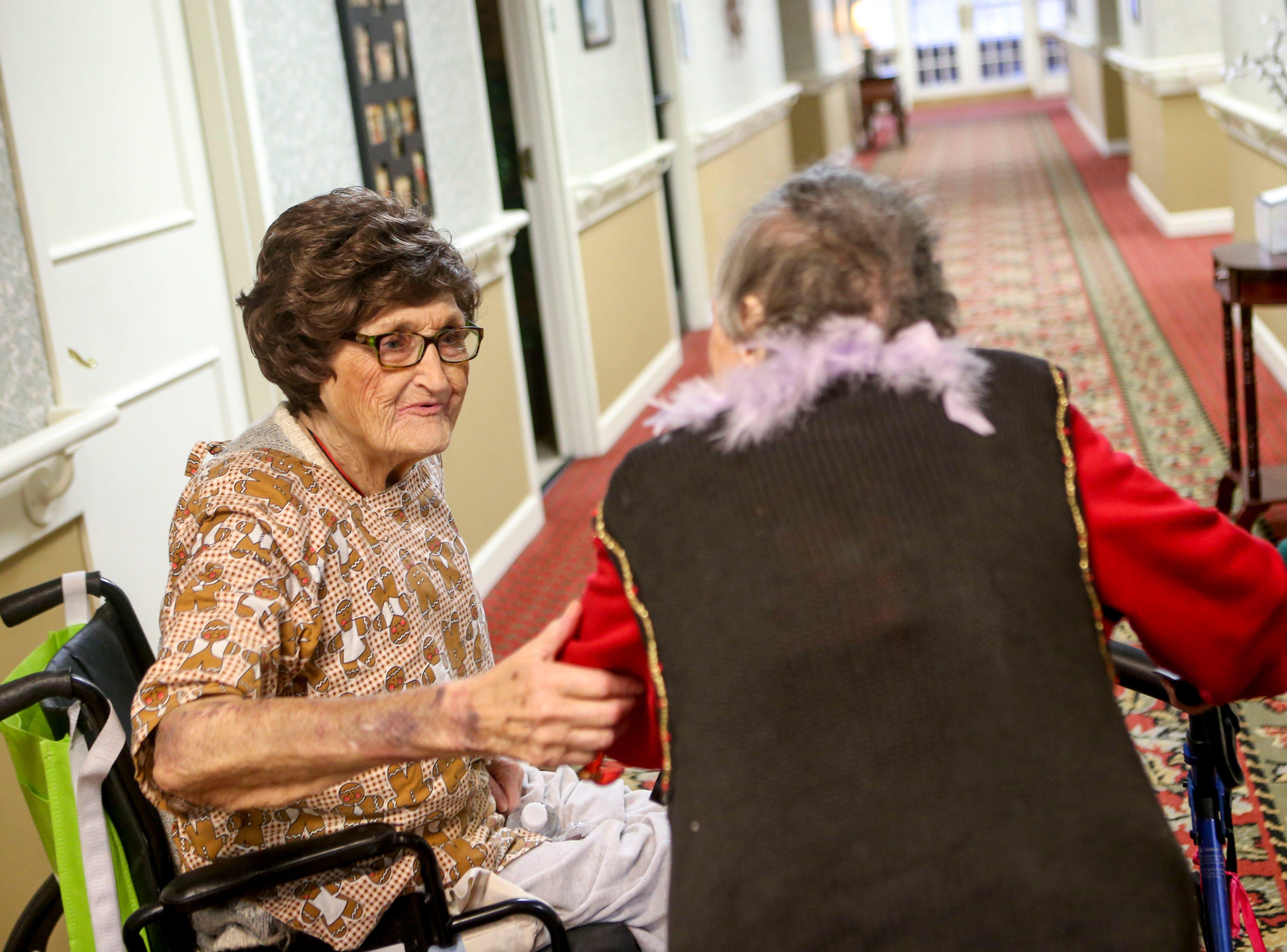 Another resident says happy birthday to Ida Feldman on her 100th birthday at Regency Retirement Home in Jackson, Tenn., on Thursday, Dec. 20, 2018.