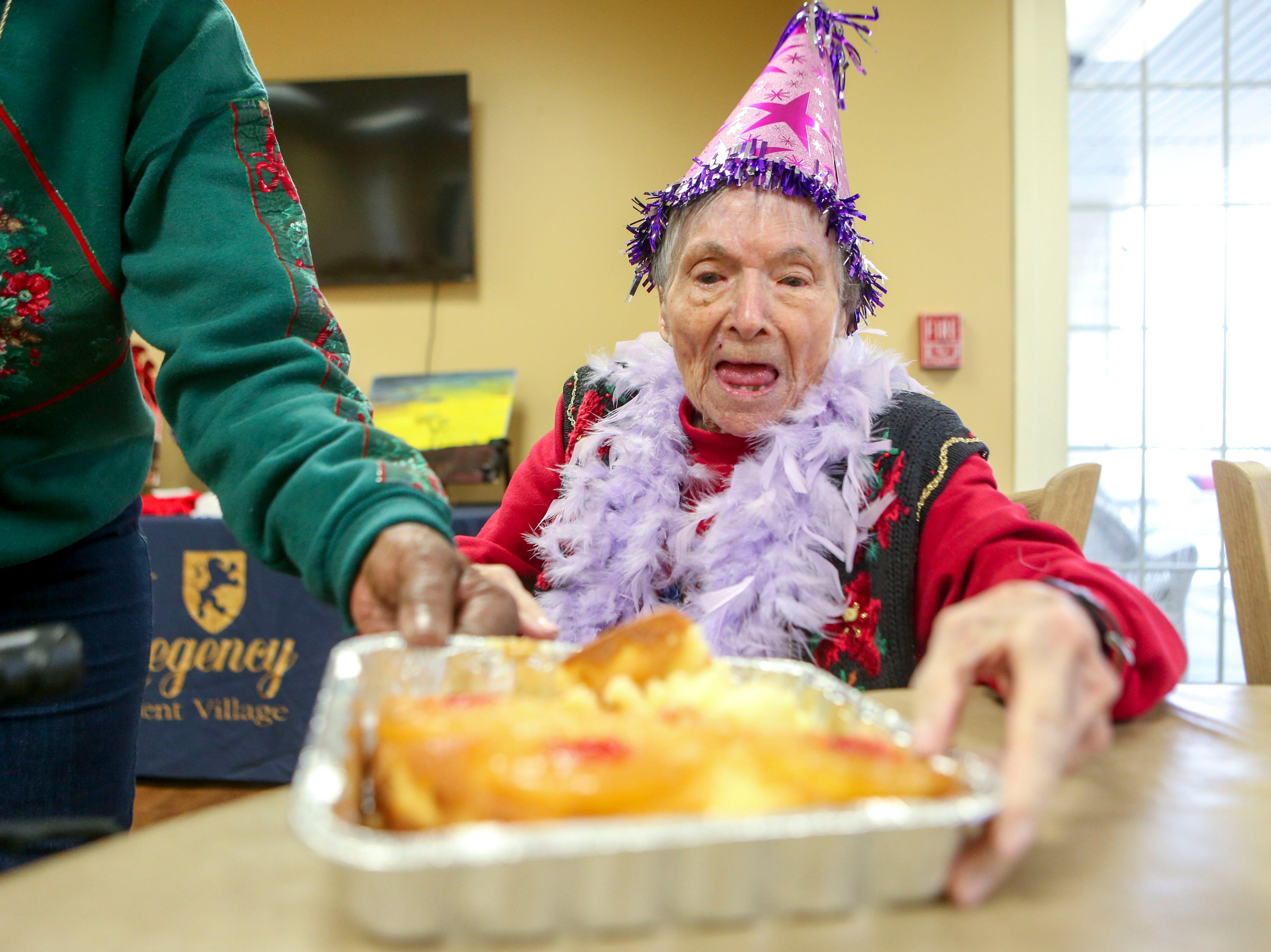 Ida Feldman looks down at her inside out pineapple cake prepared for her on her 100th birthday at Regency Retirement Home in Jackson, Tenn., on Thursday, Dec. 20, 2018.