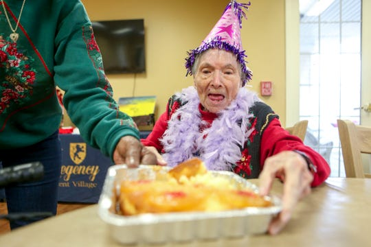 Ida Feldman looks down at her inside out pineapple cake prepared for her on her 100th birthday at Regency Retirement Home in Jackson, Tenn., on Thursday, Dec. 20, 2018.
