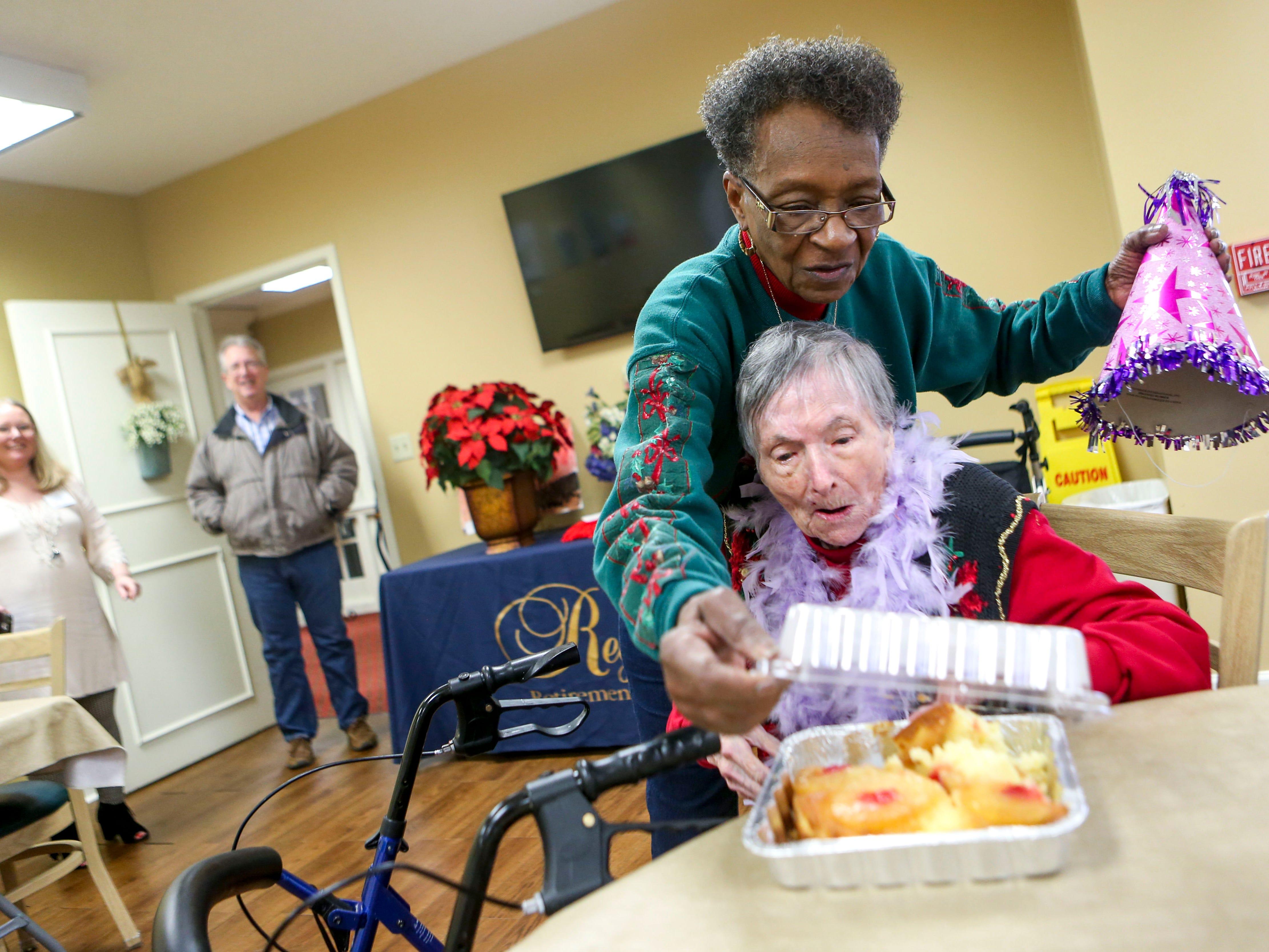 Anne Boston opens up the box for Ida Feldman's cake on Feldman's 100th birthday at Regency Retirement Home in Jackson, Tenn., on Thursday, Dec. 20, 2018.