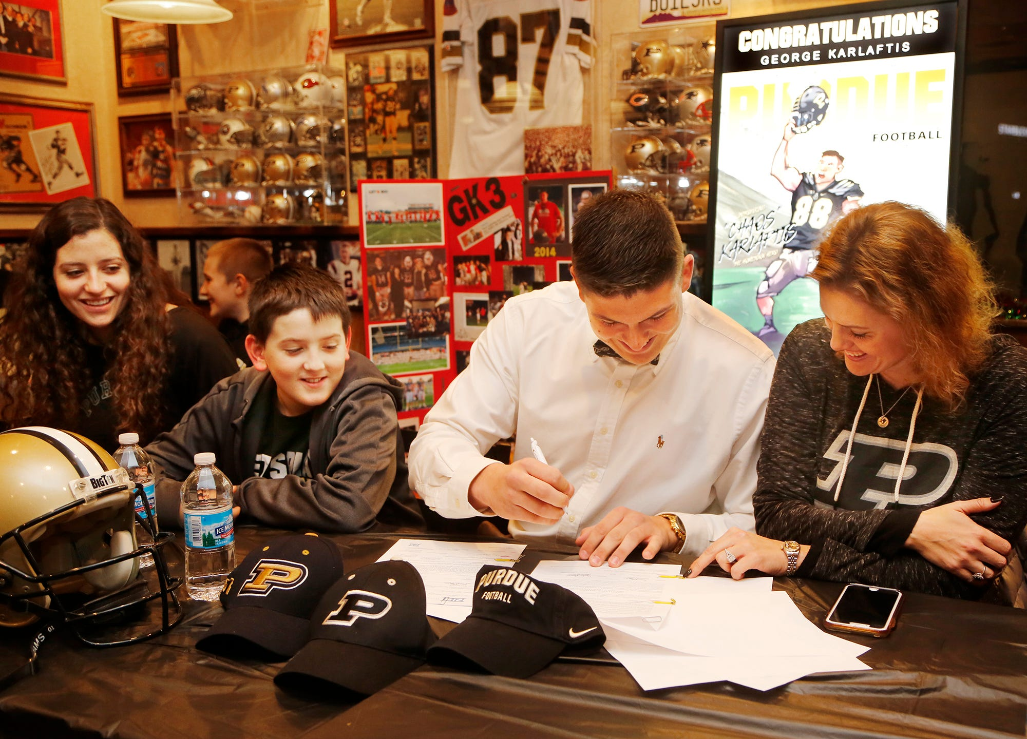 George Karlaftis of West Lafayette High School dons a Purdue cap after signing a personal copy of his national letter of intent to play football for the Boilermakers Wednesday, December 19, 2018, at Bruno's in West Lafayette. Karlaftis was joined by sister Annie, brothers Niko and Yanni and his mother Amy and numerous other friends and relatives for the event.