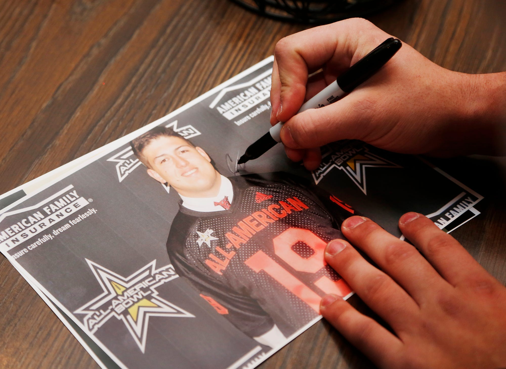 George Karlaftis signs his autograph for a fan prior to signing his personal copy of his national letter of intent to play football for Purdue Wednesday, December 19, 2018, at Bruno's in West Lafayette.