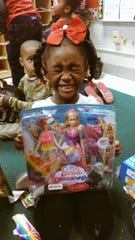 Kassidy Brown, a kindergartener at Ford Early Learning Center in Ypsilanti, is excited about the Barbie she received as part of Operation Christmas Wishes, a Brighton High School project.