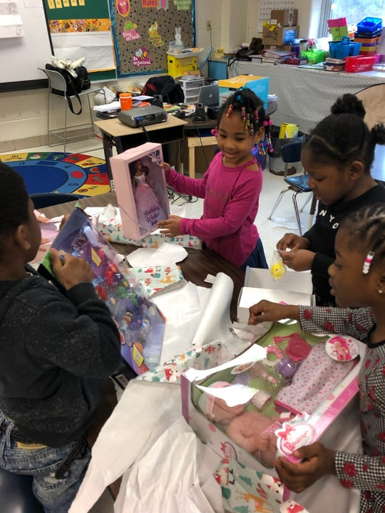 Mayana Vance, Lanajia Parker, and Solara Brainard open their gifts brought by Brighton High School students as part of Operation Christmas Wishes on Dec. 17, 2018.