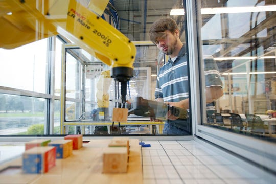 Wesley Stillions, 19, runs a program on a Fanuc robot that picks up and arranges wooden blocks inside the Ramtec training facility in Marion, Ohio on July 31, 2018. [Adam Cairns / Dispatch]