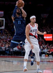 Memphis Grizzlies guard Mike Conley, left, shoots over Portland Trail Blazers guard Seth Curry during the first half of an NBA basketball game in Portland, Ore., Wednesday, Dec. 19, 2018. (AP Photo/Craig Mitchelldyer)