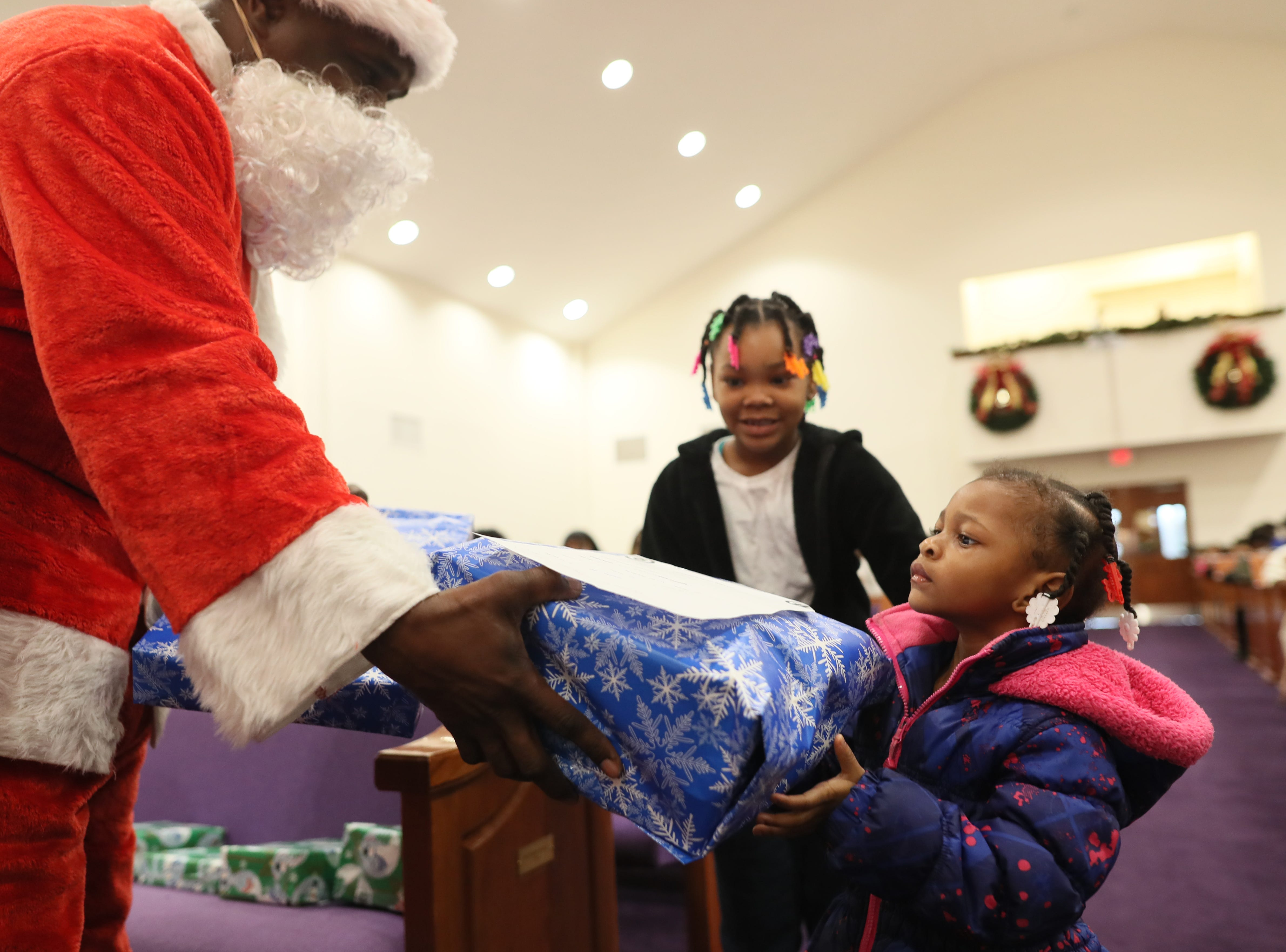 Officer Keith Payne hands out gifts dressed as Santa as the MPD's Community Outreach Program brings Christmas cheer to dozens of families at Grace Missionary Baptist Church on Thursday, Dec. 20, 2018.