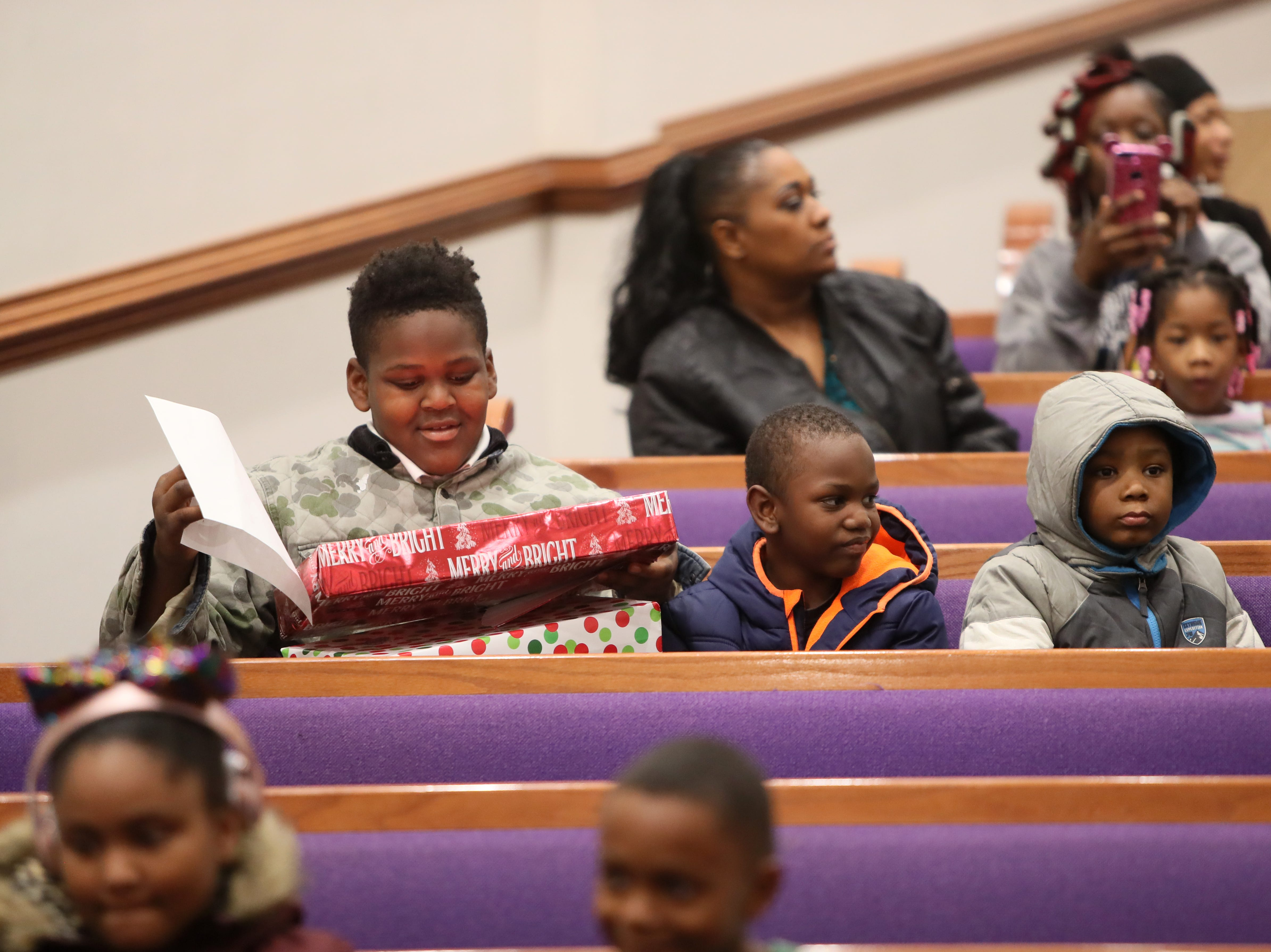 Children receive Christmas presents as the MPD's Community Outreach Program brings holiday cheer through gifts and food to dozens of families at Grace Missionary Baptist Church on Thursday, Dec. 20, 2018.