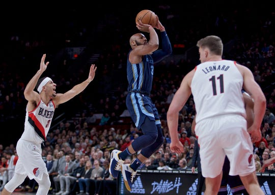 Memphis Grizzlies guard Jevon Carter, center, shoots over Portland Trail Blazers guard Seth Curry, left, and forward Meyers Leonard, right, during the first half of an NBA basketball game in Portland, Ore., Wednesday, Dec. 19, 2018. (AP Photo/Craig Mitchelldyer)