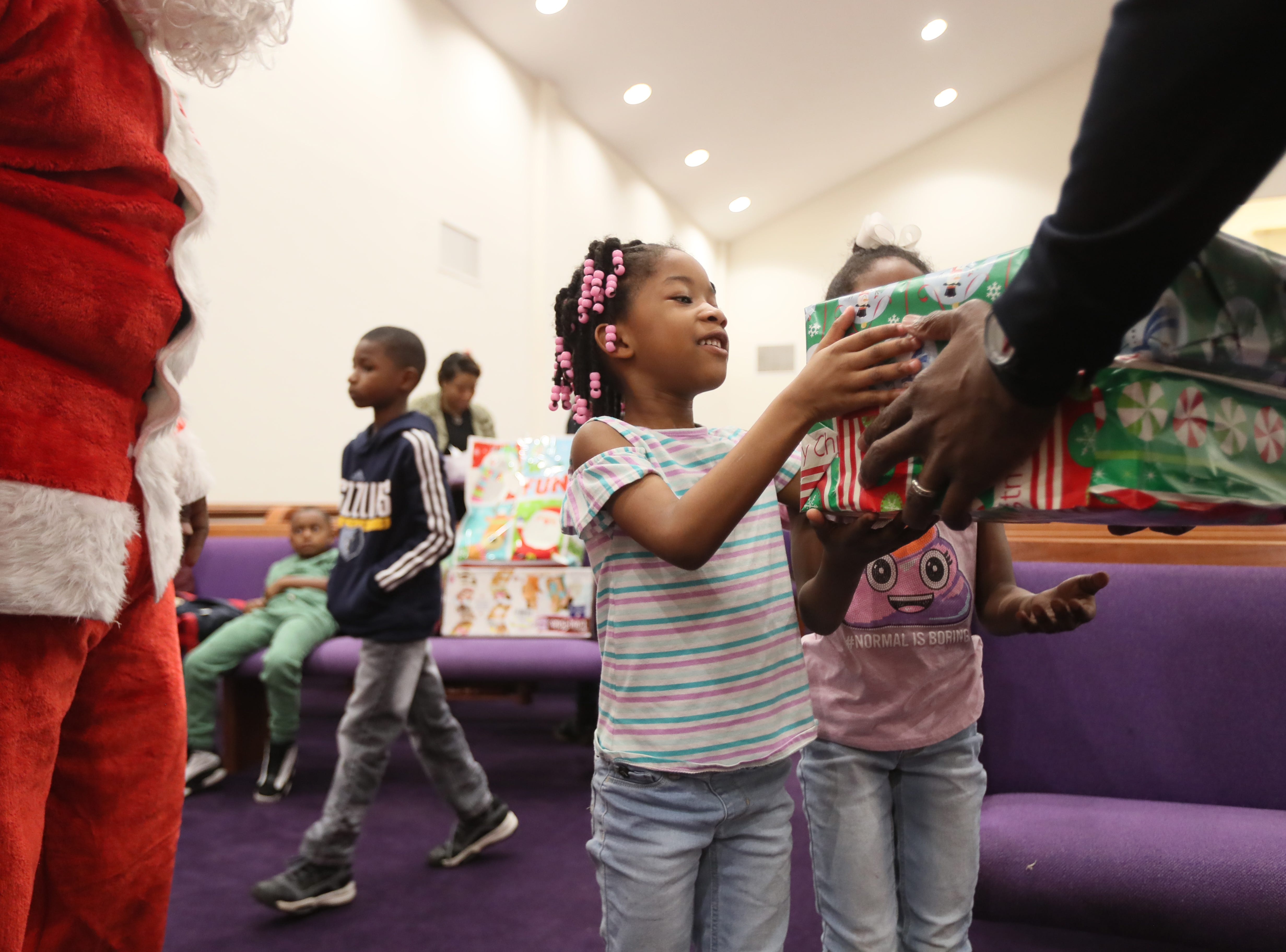 Children receive presents from the MPD's Community Outreach Program as they bring holiday cheer in the name of gifts and food to families at Grace Missionary Baptist Church on Thursday, Dec. 20, 2018.