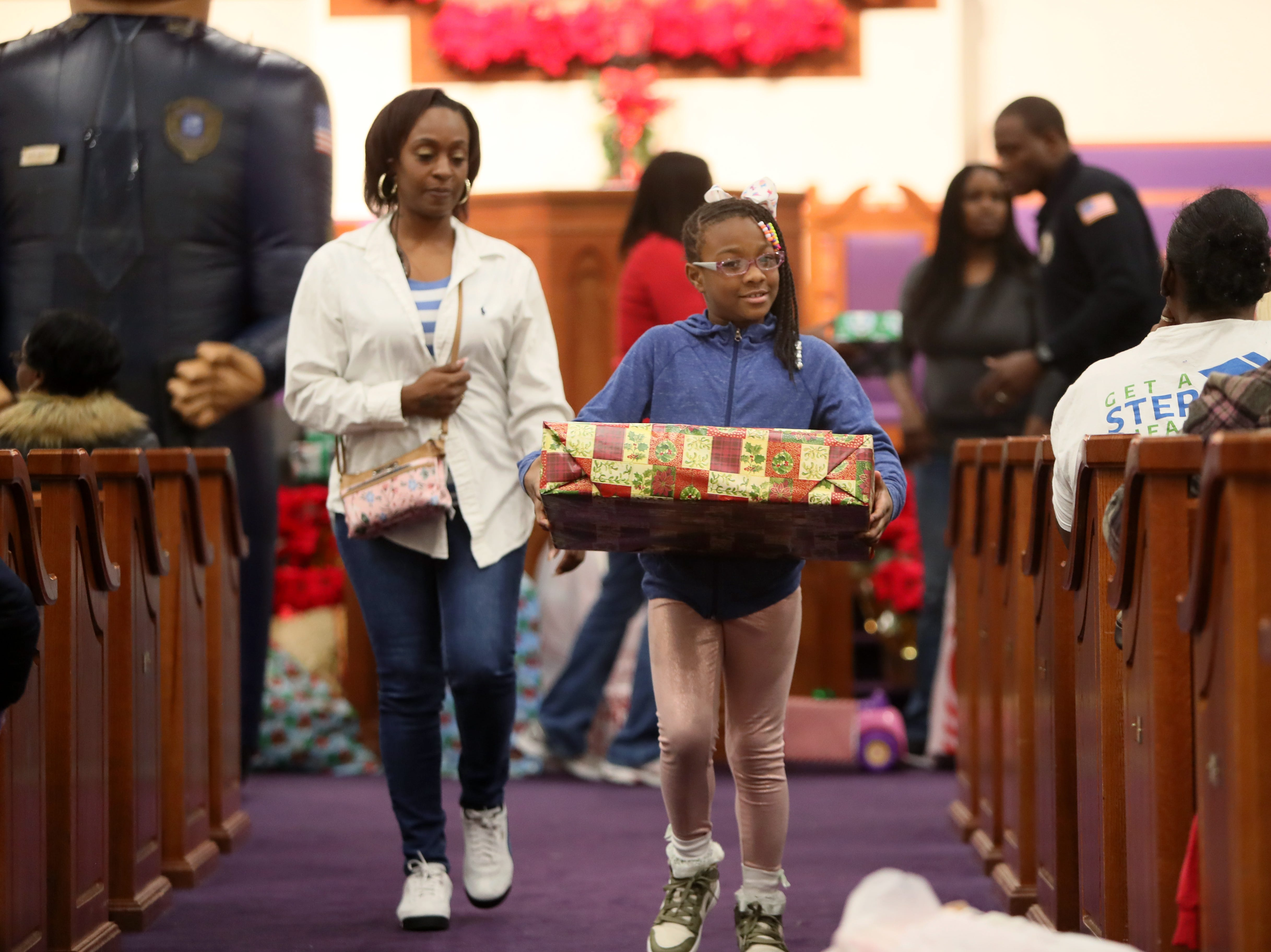Tridinal Gillespie and her daughter Sandria, 8, receive a gift from MPD's Community Outreach Program as they serve holiday cheer with presents and food for families at Grace Missionary Baptist Church on Thursday, Dec. 20, 2018.