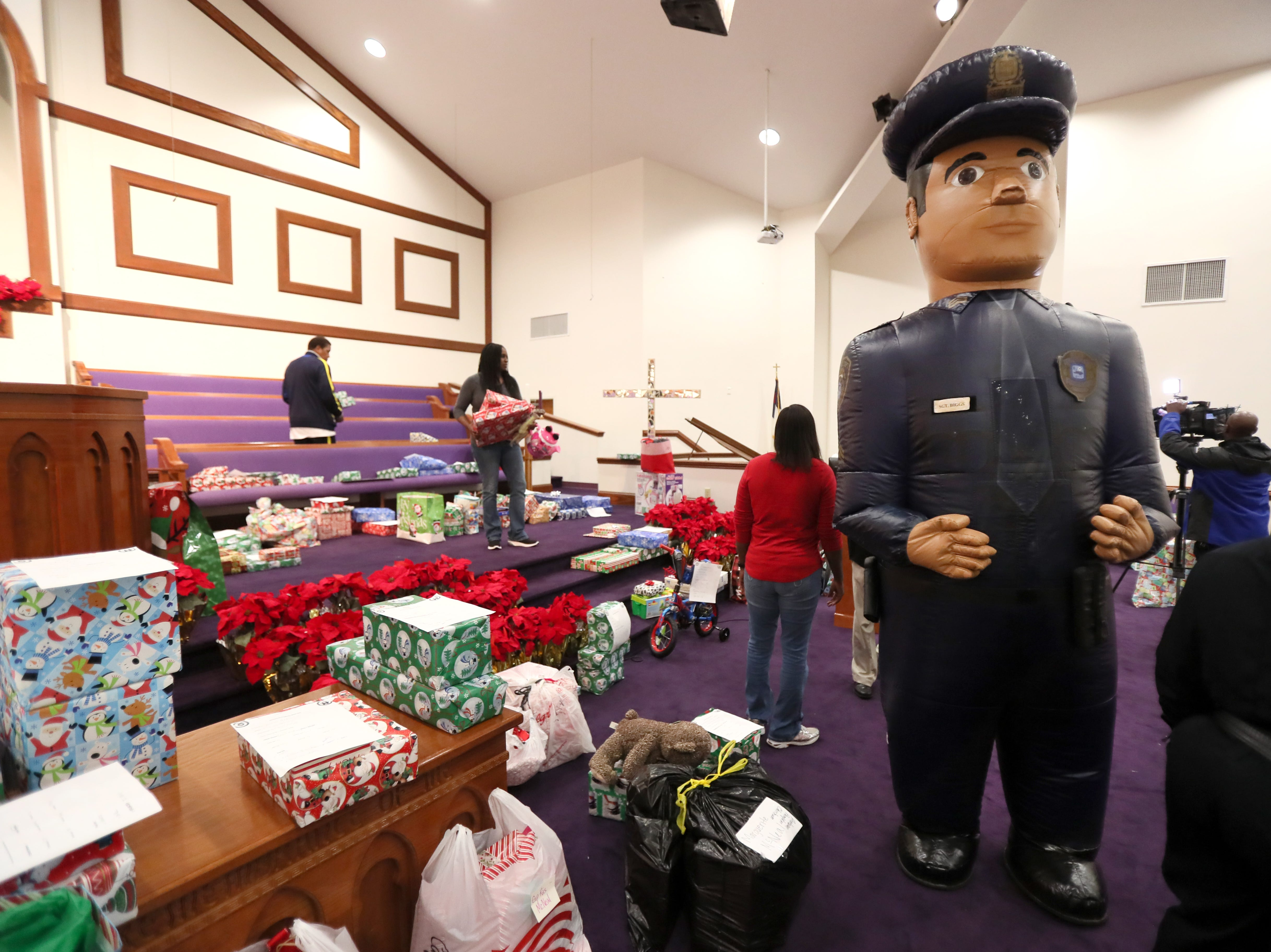 'Sgt. Biggs', MPD's Community Outreach Program mascot delights children as the unit brings Christmas cheer to families at Grace Missionary Baptist Church on Thursday, Dec. 20, 2018.