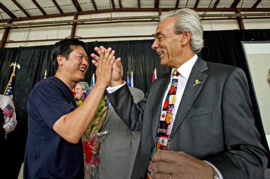 Wei Chen, left, gets a high-five from ALSAC CEO Richard C. Shadyac Jr. in a hangar at Wilson Air Center after Chen landed at Memphis International Airport, completing a 70-day trip around the globe, on July 29, 2011. Chen was the first Chinese citizen to complete the journey, which he undertook to benefit St. Jude Children's Research Hospital.