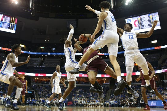 Memphis Tigers defenders Kareem Brewton Jr., from left, Kyvon Davenport, Isaiah Maurice and Victor Enoh shut down the shot of Arkansas-Little Rock Trojans guard Rayjon Tucker during their game at the FedExForum on Wednesday, Dec. 19, 2018.