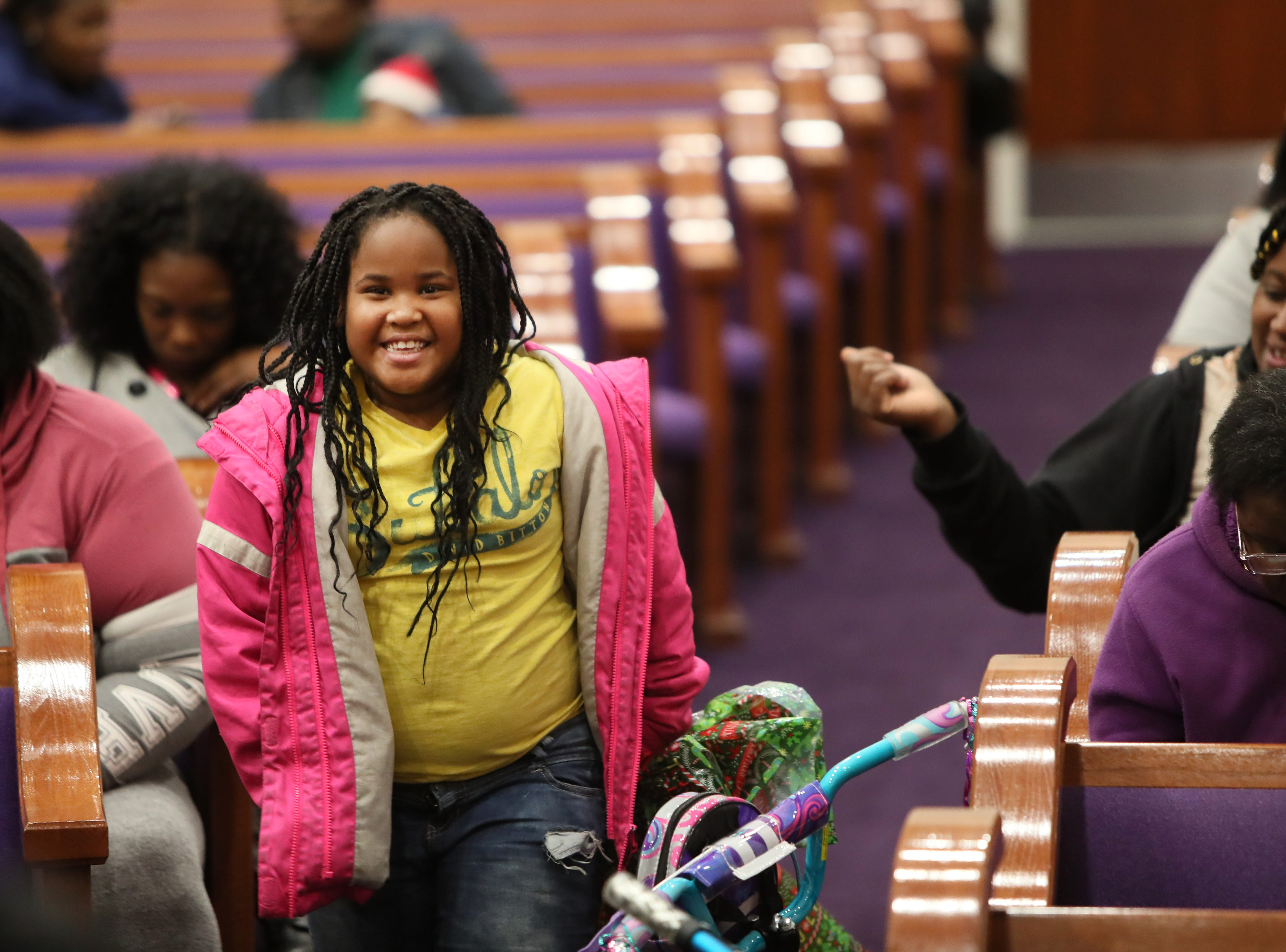 Natiyah Fason, 8, smiles as she receives a present from the MPD's Community Outreach Program at Grace Missionary Baptist Church on Thursday, Dec. 20, 2018.
