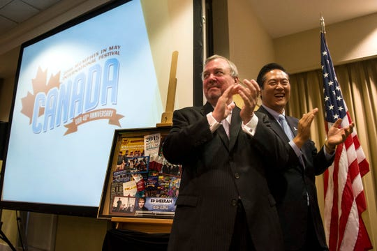 Memphis In May International Festival President and CEO Jim Holt, left, and Wei Chen, MIM 2015 chairman of the board of directors, applaud after revealing Canada as the 2016 MIM honored country during the group's annual meeting Aug. 13, 2015, at the Memphis Botanic Garden.