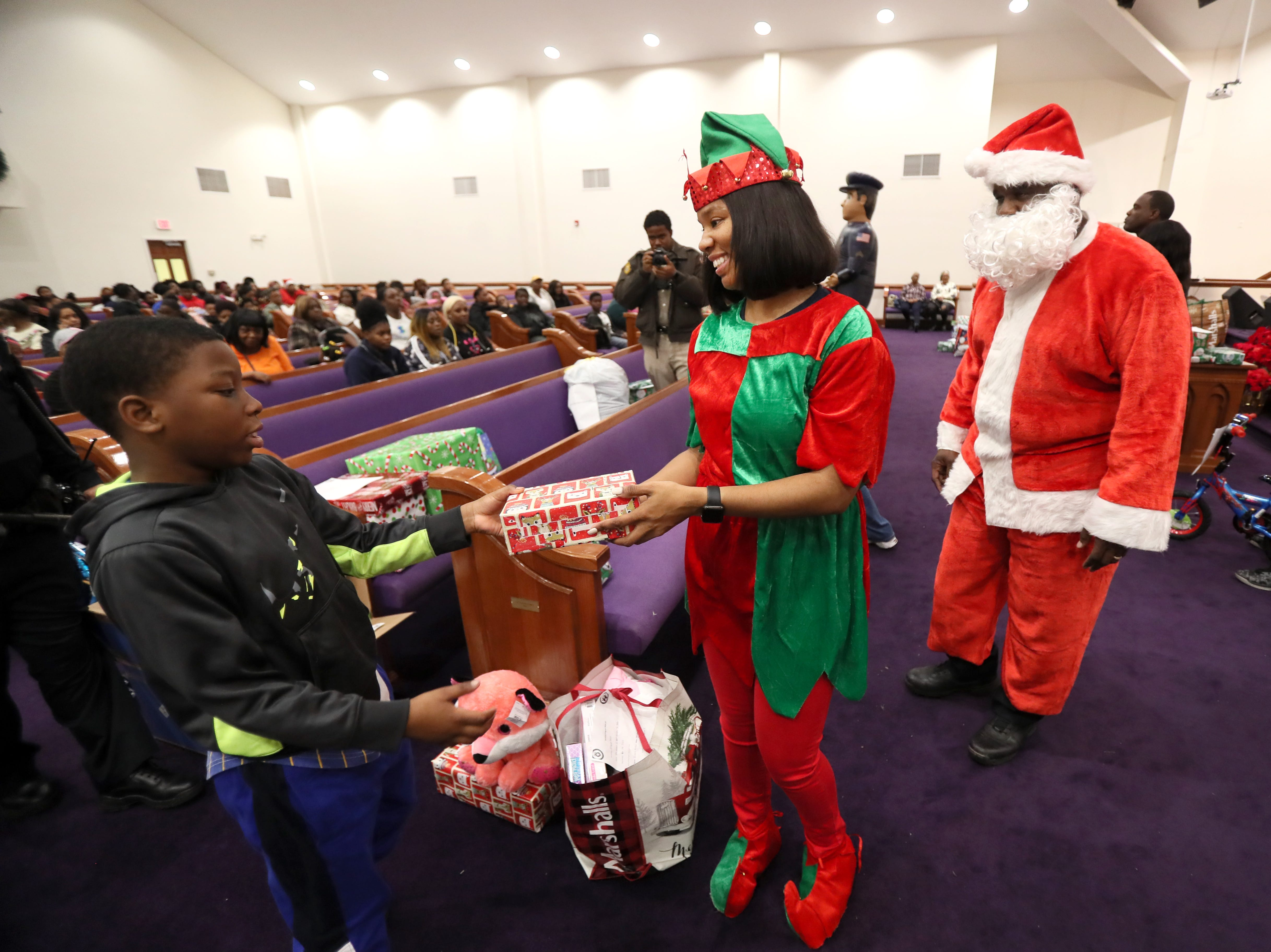 Officer Dominique McCraven hands out gifts dressed as an elf as the MPD's Community Outreach Program brings Christmas cheer to dozens of families at Grace Missionary Baptist Church on Thursday, Dec. 20, 2018.