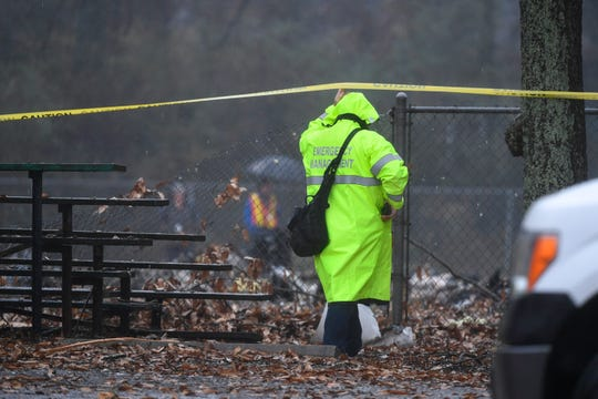An investigator works the scene of a small plane crash in a city park which killed all on board, Thursday, Dec. 20, 2018, in northwest Atlanta. (AP Photo/John Amis)