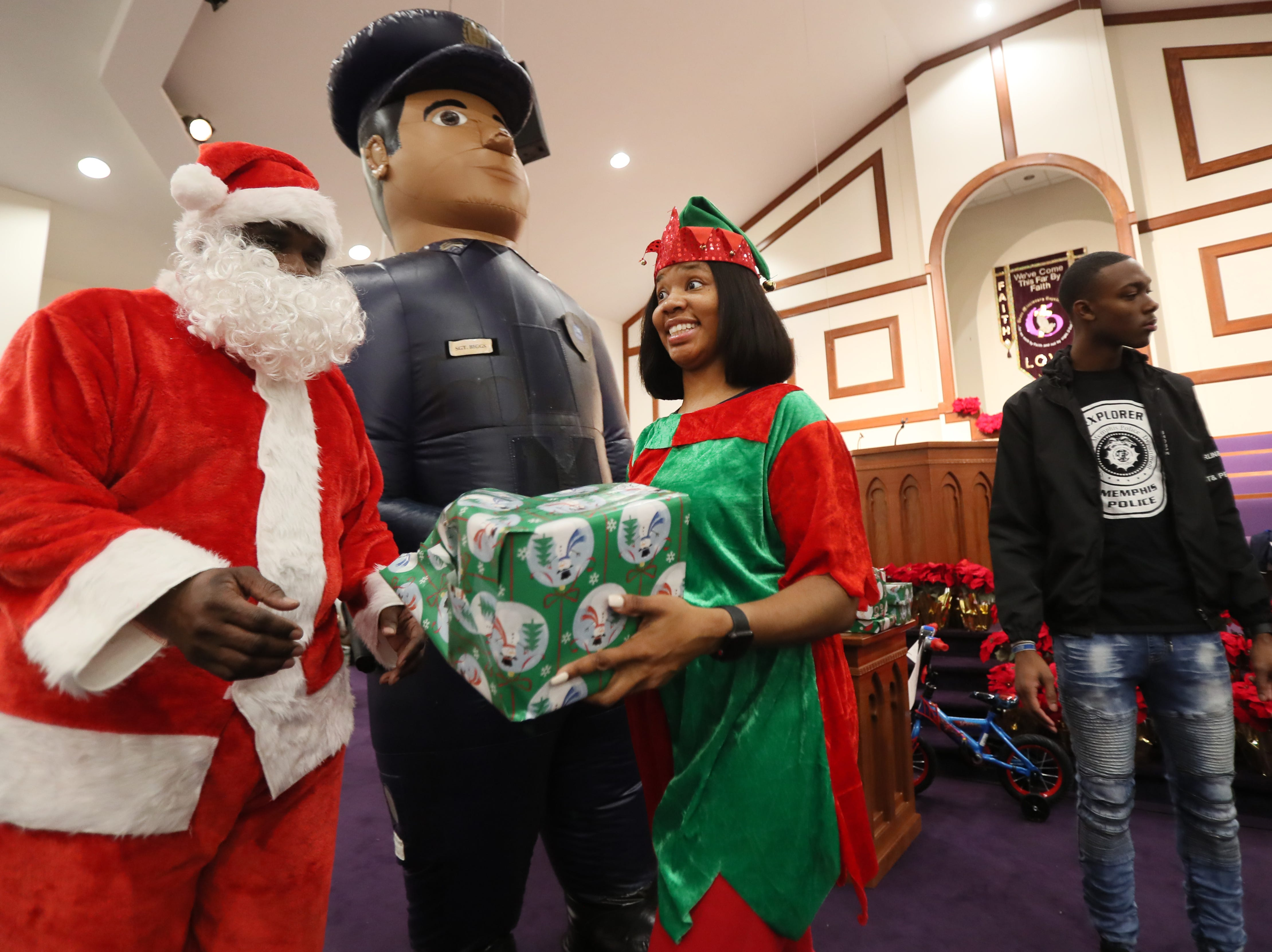 Officers Dominique McCraven, dressed as an elf and  Keith Payne as Santa, hand out gifts and as the MPD's Community Outreach Program brings Christmas cheer to dozens of families at Grace Missionary Baptist Church on Thursday, Dec. 20, 2018.