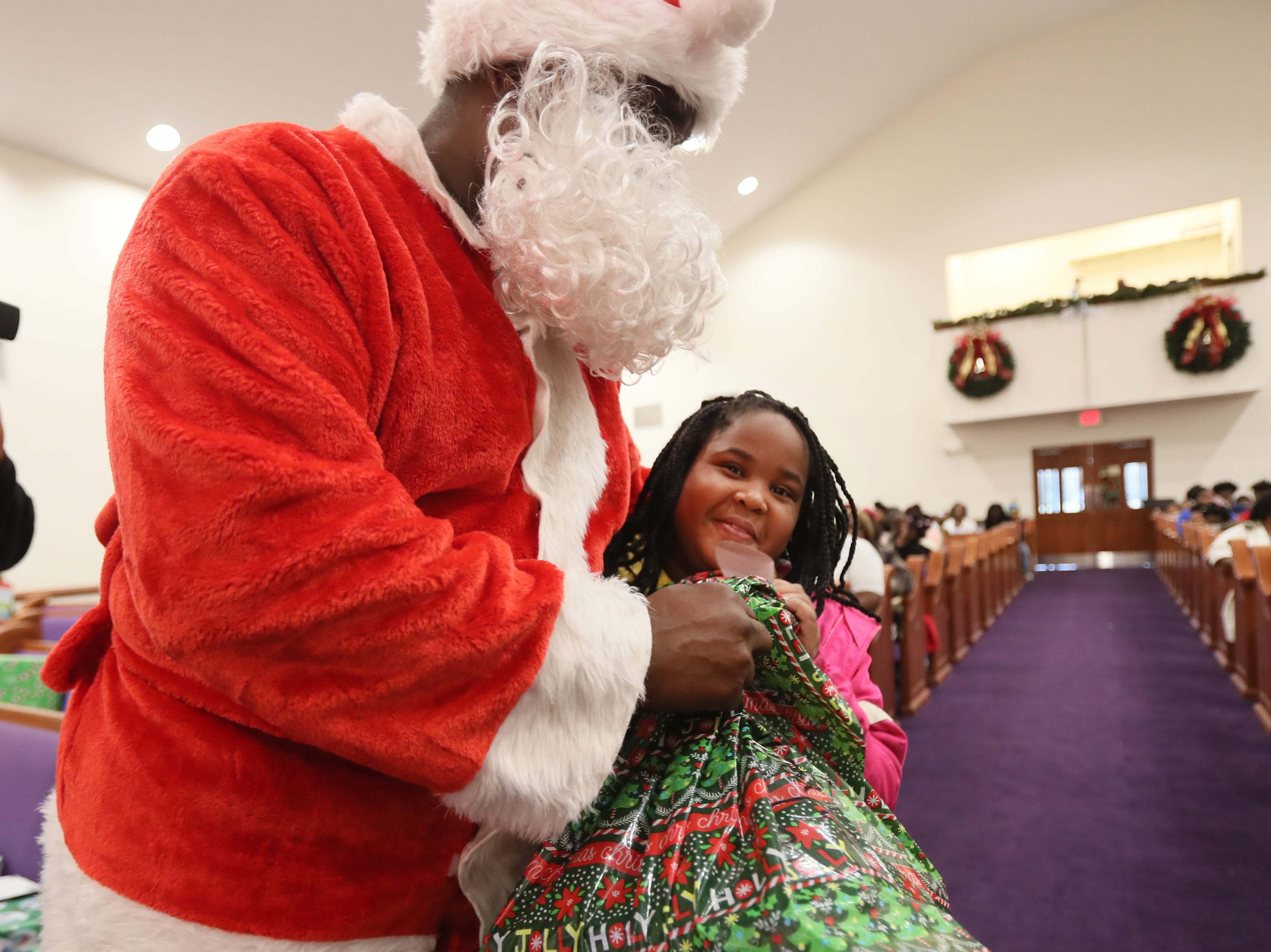 Officer Keith Payne hands out gifts dressed as Santa to Natiyah Fason, 8, as the MPD's Community Outreach Program brings Christmas cheer to dozens of families at Grace Missionary Baptist Church on Thursday, Dec. 20, 2018.