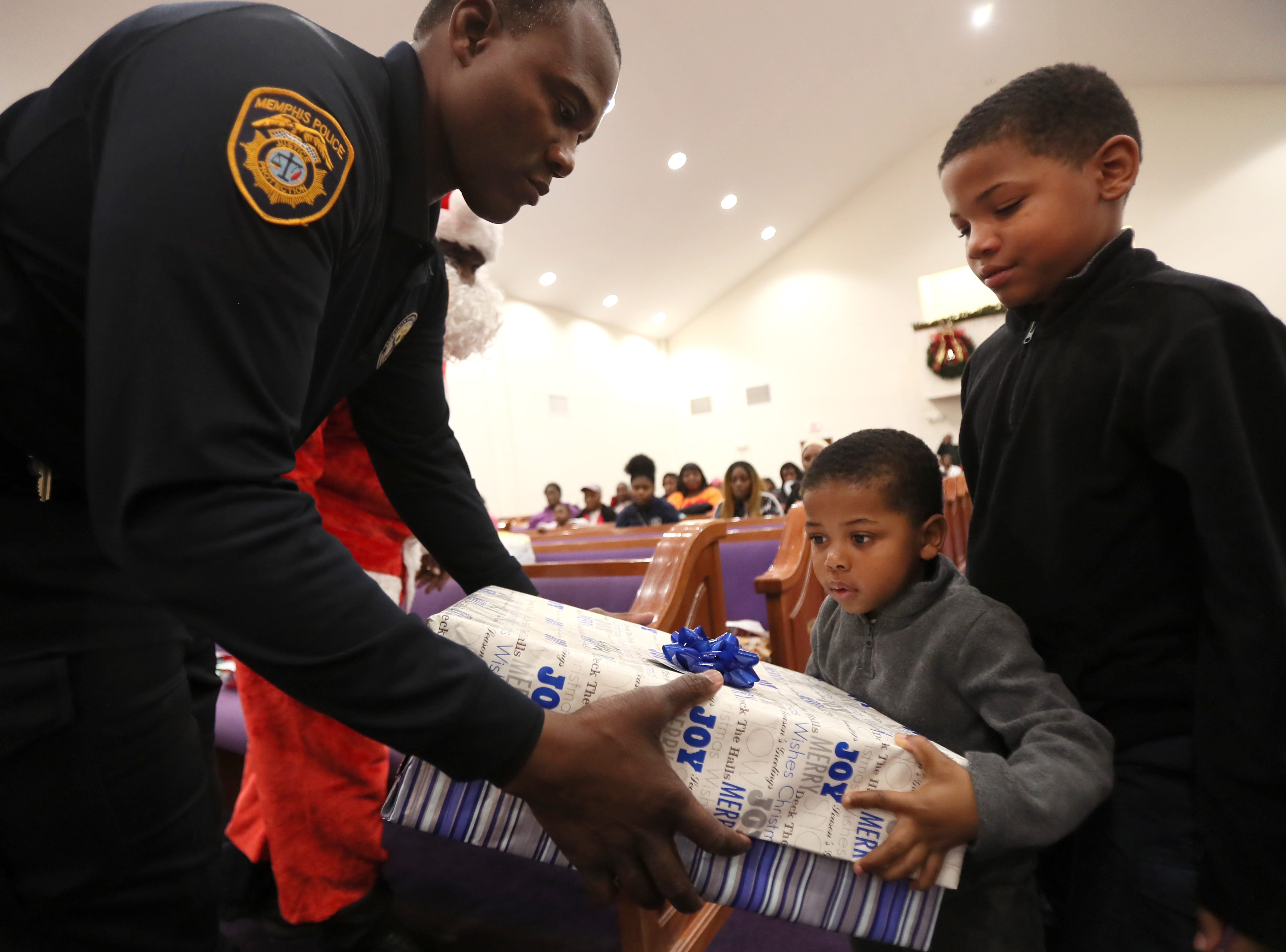Officer Clayton Turner hands out gifts to brothers Chase, 3, and Peyton Glover, 9, as the MPD's Community Outreach Program brings Christmas cheer to dozens of families at Grace Missionary Baptist Church on Thursday, Dec. 20, 2018.