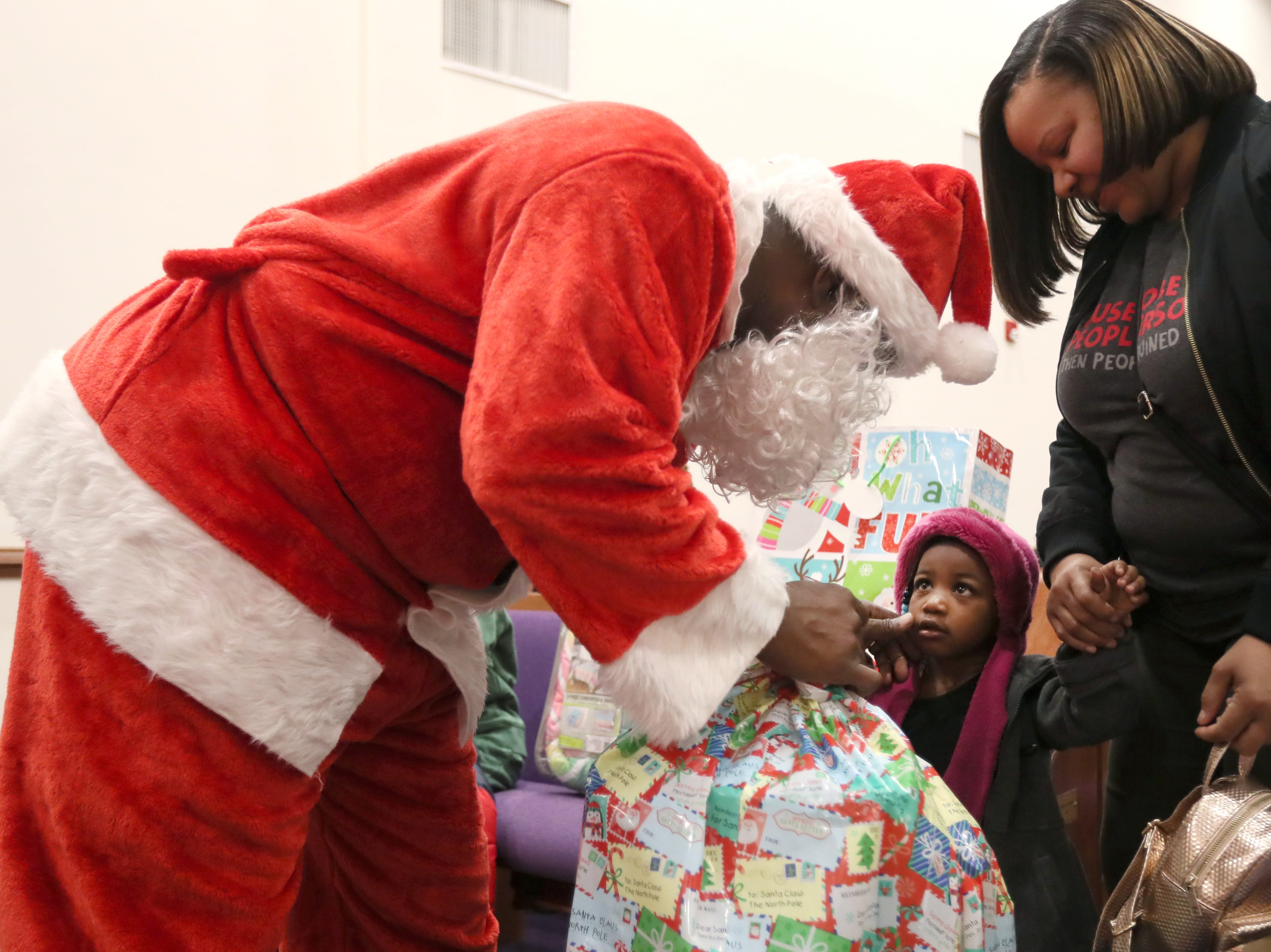 Officer Keith Payne, dressed as Santa, pinches the cheek of Miaya Carlock, 2, with her grandmother Mary Beasley by her side as the MPD's Community Outreach Program brings Christmas cheer to dozens of families at Grace Missionary Baptist Church on Thursday, Dec. 20, 2018.