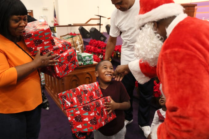 Officer Keith Payne hands out gifts dressed as Santa to a smiling Christian Williams, 6, as the MPD's Community Outreach Program brings Christmas cheer to dozens of families at Grace Missionary Baptist Church on Thursday, Dec. 20, 2018.