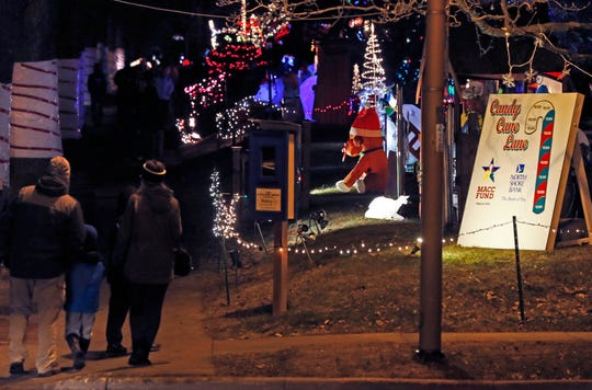 Families take advantage of the mild weather to walk the streets of Candy Cane Lane in West Allis during a past year's display. This year's event is open through Dec. 28.
