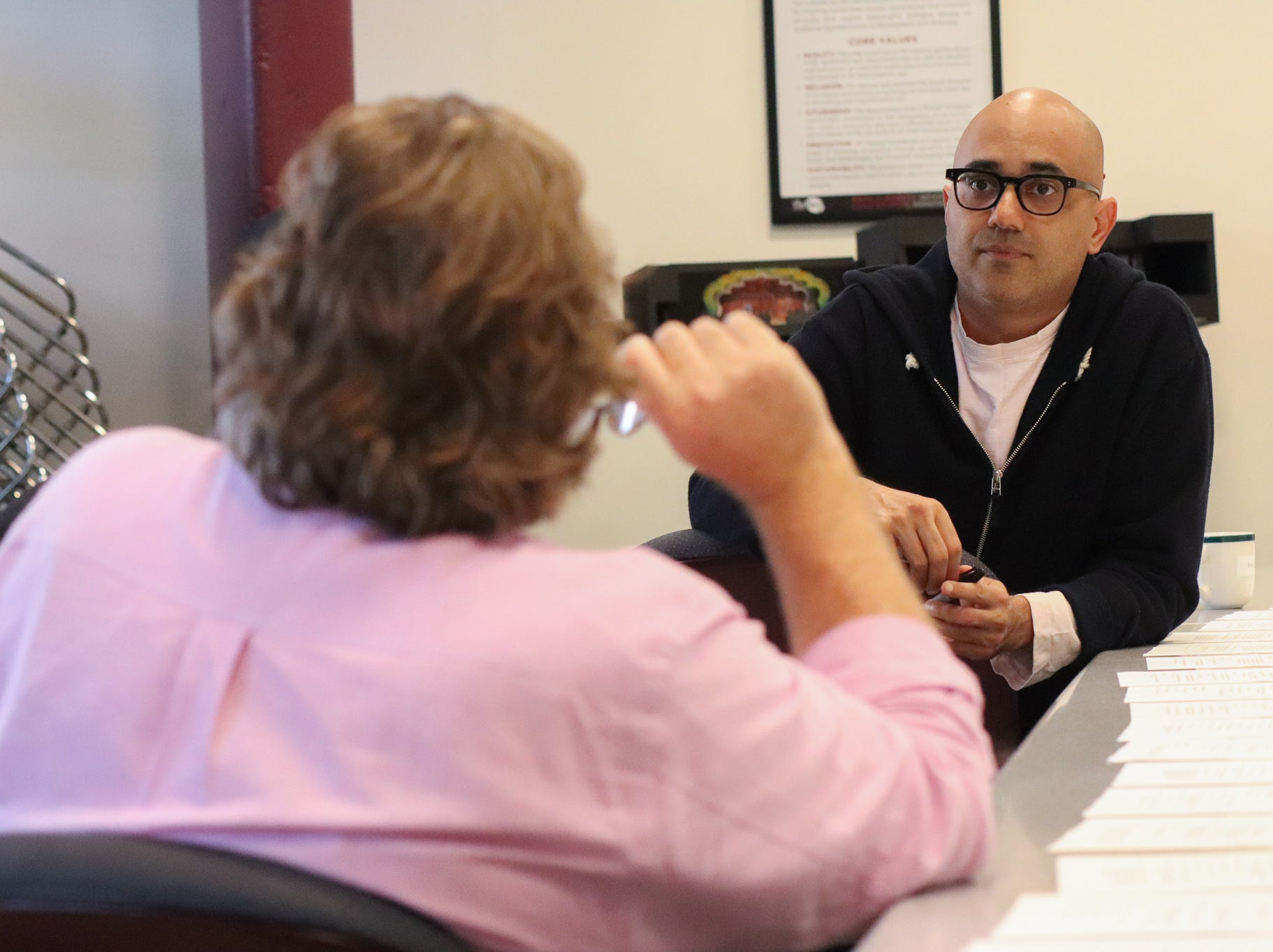 "Director Mark Clements (left) confers with playwright Ayad Akhtar about ""Junk."" The Milwaukee Repertory Theater's production begins Jan. 15."