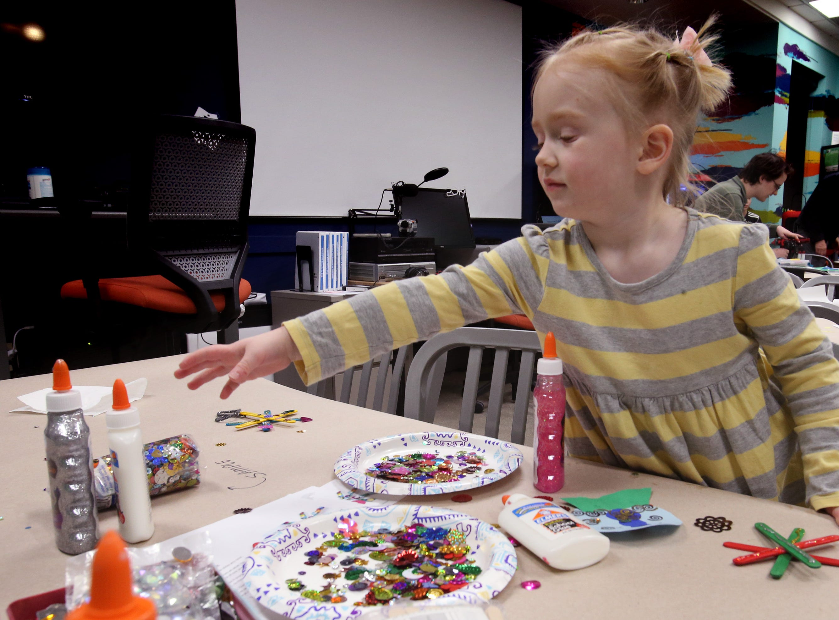 Amerlia Merkle, 4, reaches for glitter glue while making a sparkle snowflake during a holiday ornament workshop in the Mukwonago Community Library's MetaSpace 511 on Dec. 19.