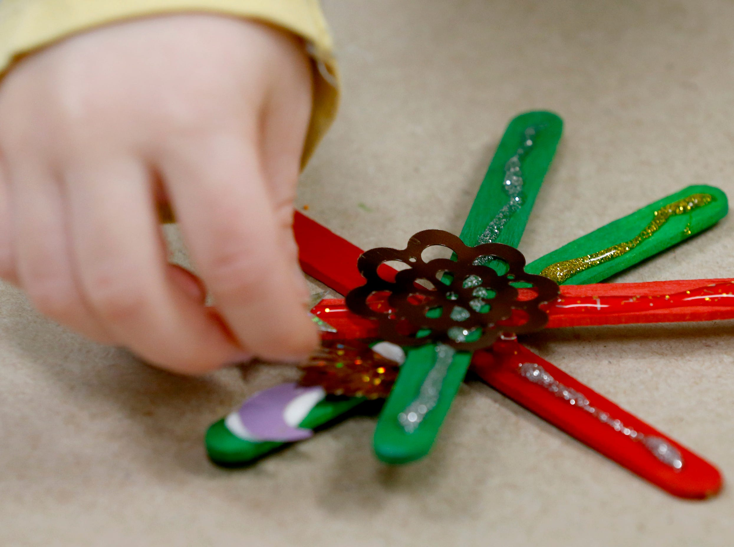 Amerlia Merkle, 4, adds sparkles to her snowflake during a holiday ornament workshop in the Mukwonago Community Library's MetaSpace 511 on Dec. 19.