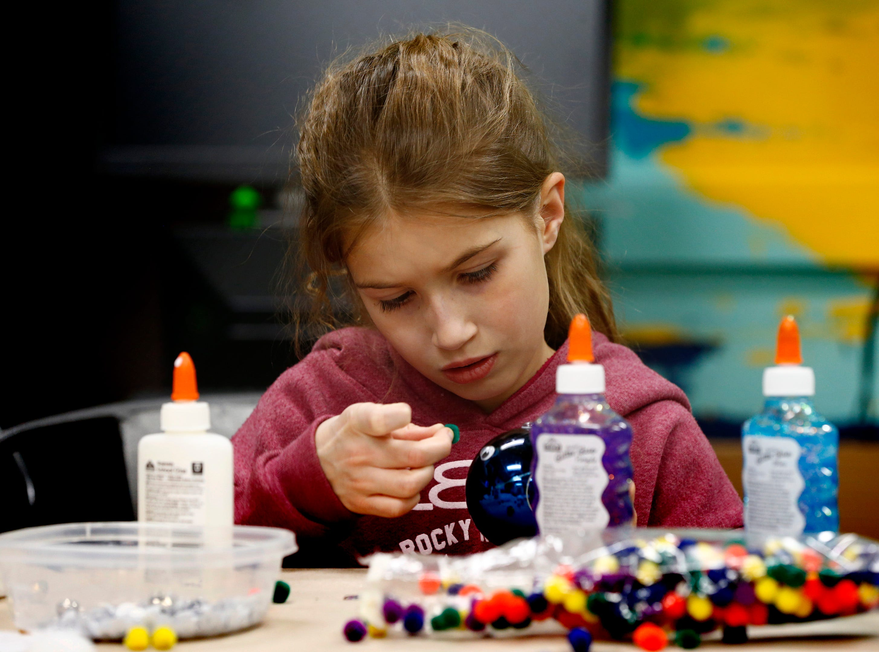 Emmalynn Podgorski, 9, adds glues on pompons during a holiday ornament workshop in the Mukwonago Community Library's MetaSpace 511 on Dec. 19.