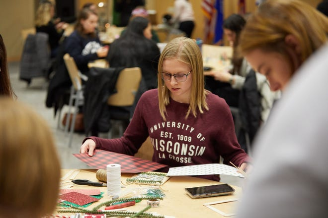 Jenna Zimmerman, a first-year student from Cleveland, Minnesota, majoring in cellular and molecular biology at UW-La Crosse, works on a holiday decoration as a money-saving strategy.