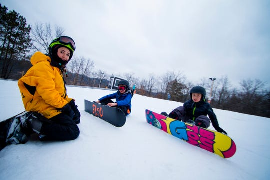 Snowboarders sit at the top of a run at Tyrol Basin in Mount Horeb.