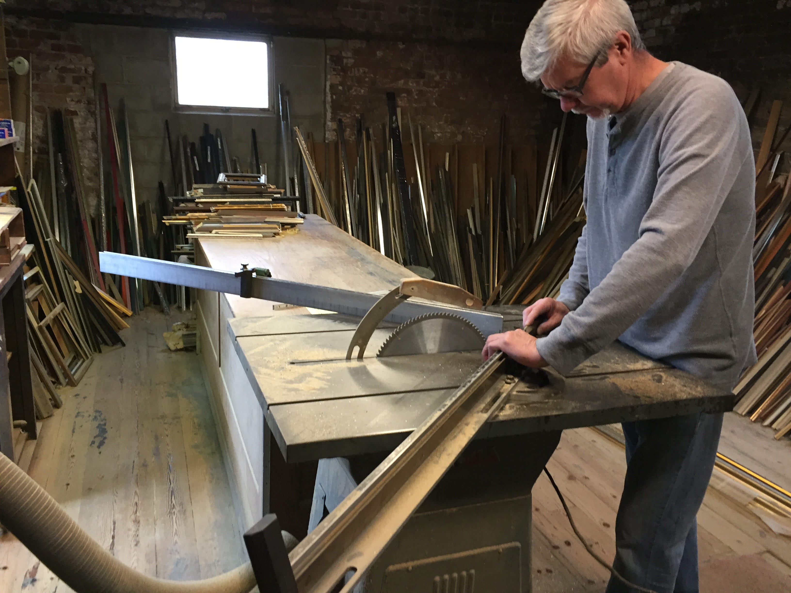 Dennis Roddy, one of the owners of Milwaukee Moulding & Frame, stands at the table saw in the shop's second-floor workshop.