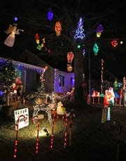 Families take advantage of mild weather to walk the streets of Candy Cane Lane in West Allis in 2018. The annual display, opening Nov. 29, raises money for the MACC Fund - Midwest Athletes Against Childhood Cancer.
