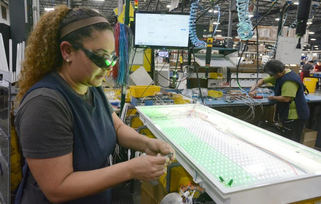 Keisy Toro assembles LED lighting fixtures at Kenall Manufacturing Co. in April 2017. Kenall makes a variety of lighting products at its factory and headquarters in Kenosha.
