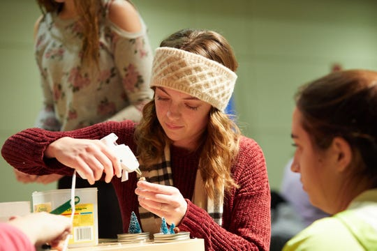 "Marissa Duggan, a freshman biology major at UW-La Crosse from Waukesha, uses a glue gun to prepare a tiny tree for a tiny snow globe during a ""holiday crafts on a budget"" event before winter break. The event was sponsored by the campus ""It Make$ Cents"" money management center."