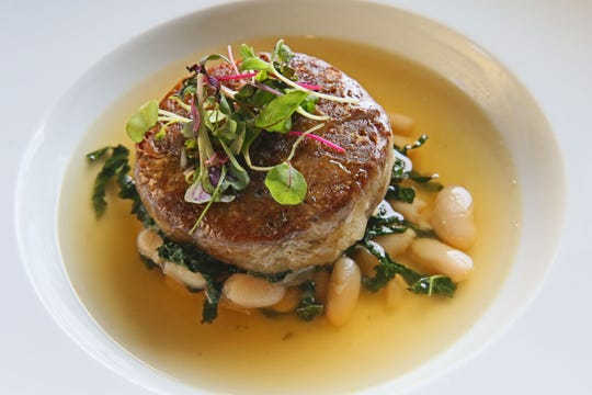 A pork crepinette, or sausage patty, is served with white beans and braised kale in pork broth as an entree at Mistral, 2473 S. Kinnickinnic Ave.