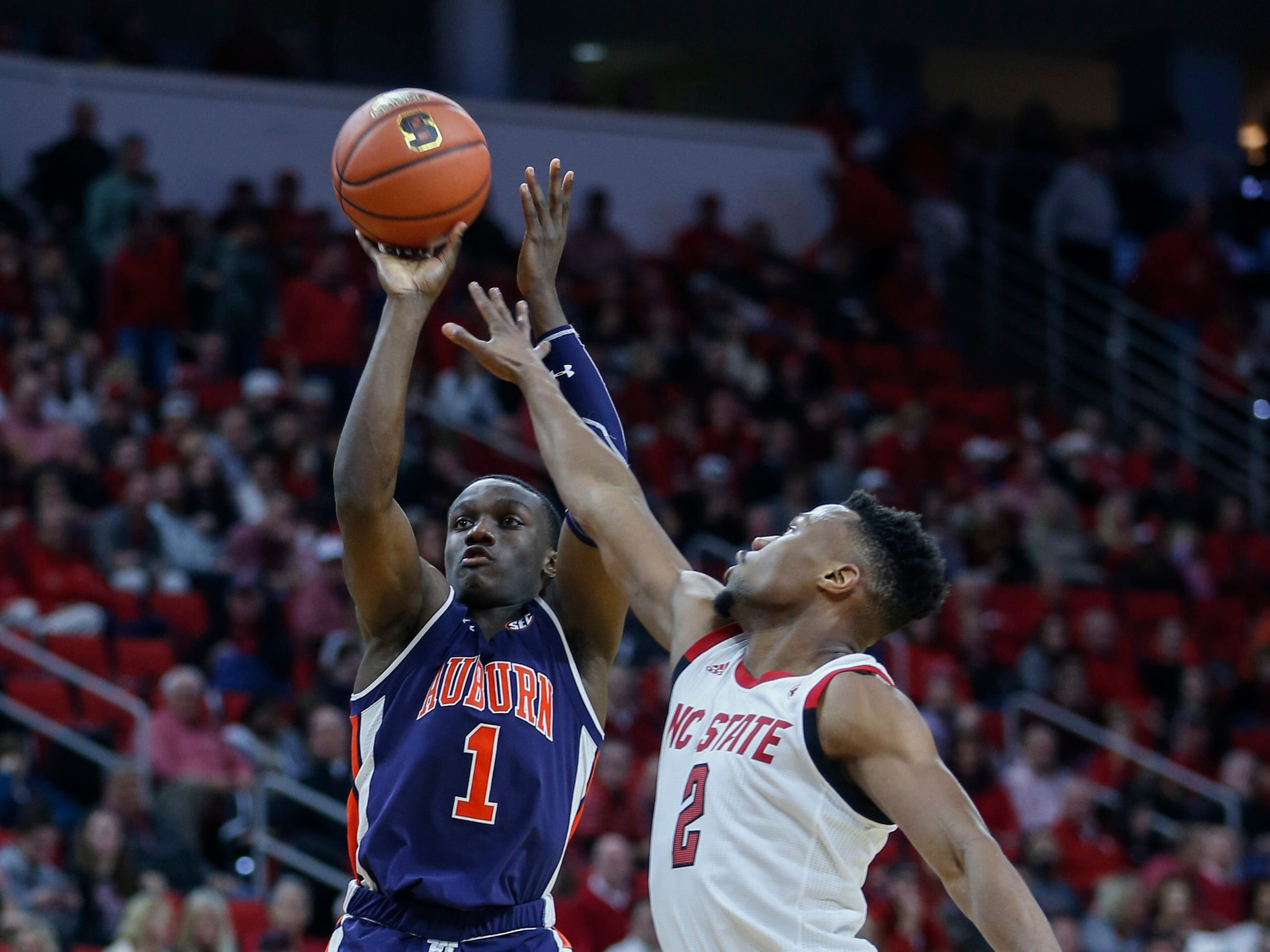 Dec 19, 2018; Raleigh, NC, USA; Auburn Tigers guard Jared Harper (1) shoots against North Carolina State Wolfpack guard Torin Dorn in the second half at PNC Arena. The North Carolina State Wolfpack won 78-71. Mandatory Credit: Nell Redmond-USA TODAY Sports