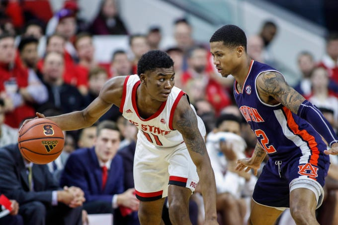 Dec 19, 2018; Raleigh, NC, USA; North Carolina State Wolfpack guard Markell Johnson (11) controls the ball against Auburn Tigers guard J'Von McCormick in the second half at PNC Arena. The North Carolina State Wolfpack won 78-71. Mandatory Credit: Nell Redmond-USA TODAY Sports