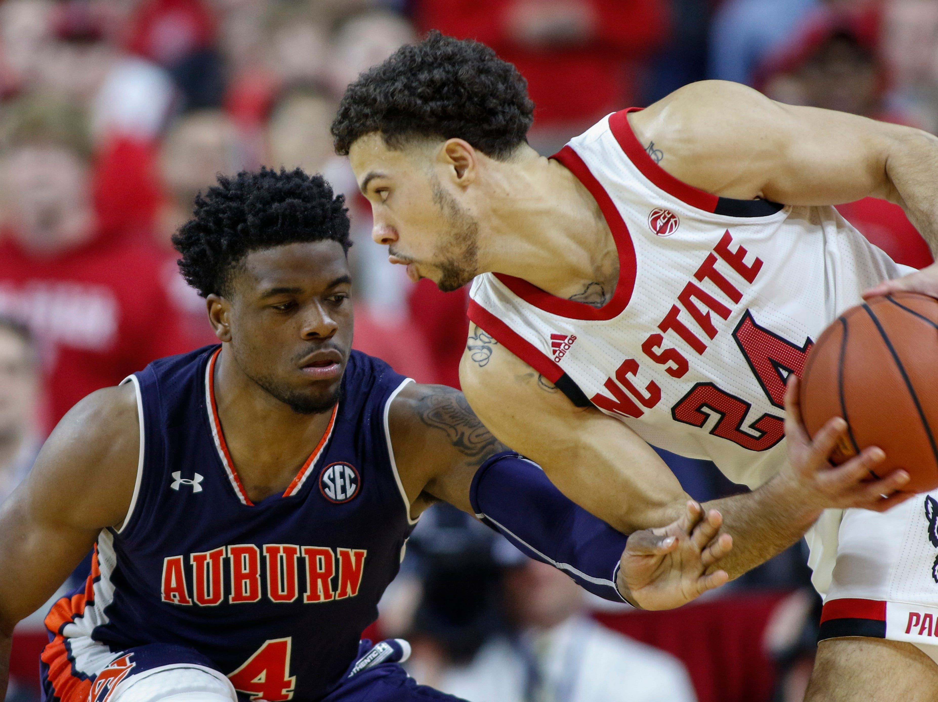 Dec 19, 2018; Raleigh, NC, USA; North Carolina State Wolfpack guard Devon Daniels (24) looks to drive against Auburn Tigers guard Malik Dunbar (4) in the second half at PNC Arena. The North Carolina State Wolfpack won 78-71. Mandatory Credit: Nell Redmond-USA TODAY Sports