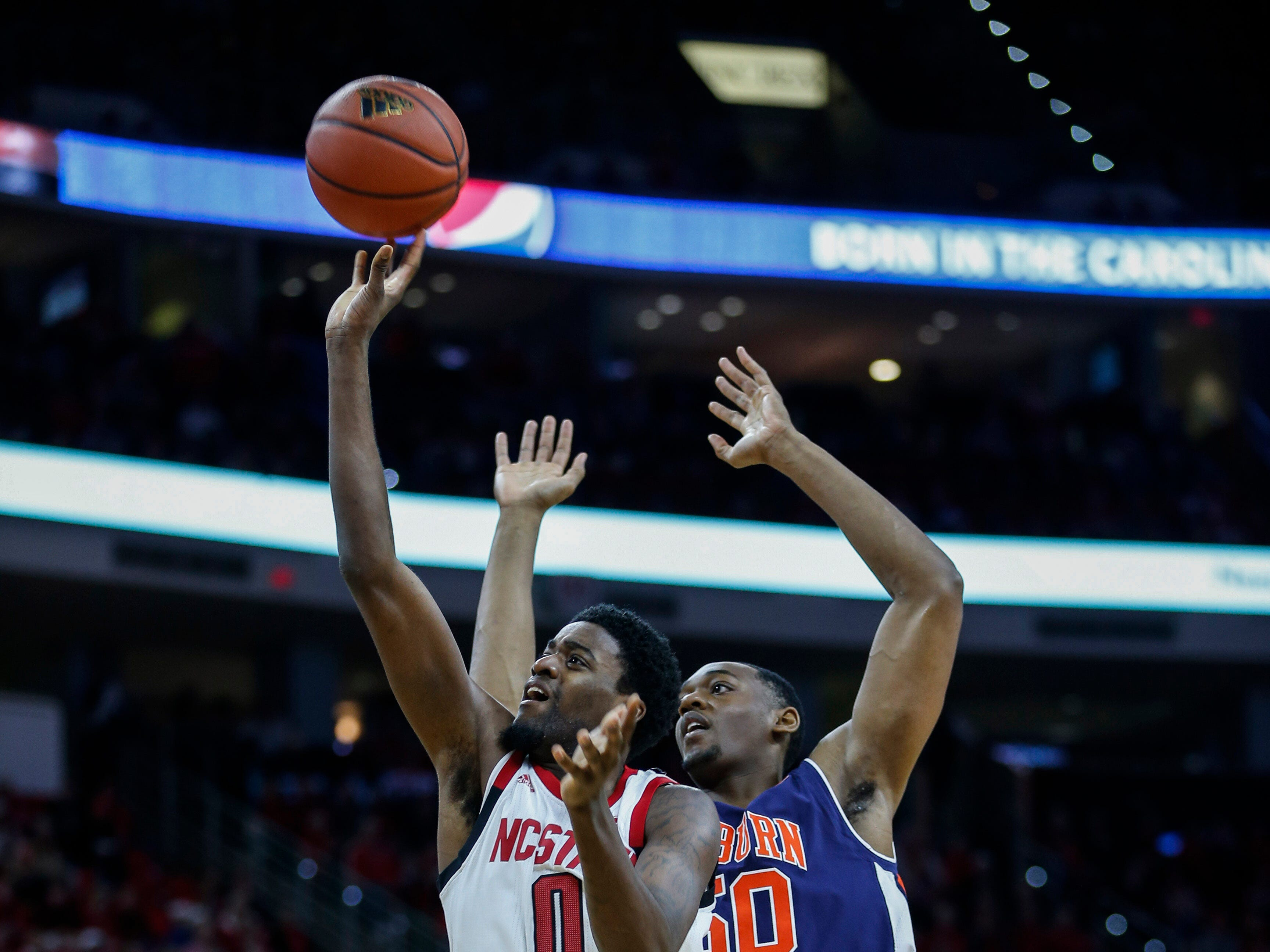 Dec 19, 2018; Raleigh, NC, USA; North Carolina State Wolfpack forward DJ Funderburk (0) shoots against Auburn Tigers center Austin Wiley in the first half at PNC Arena. Mandatory Credit: Nell Redmond-USA TODAY Sports