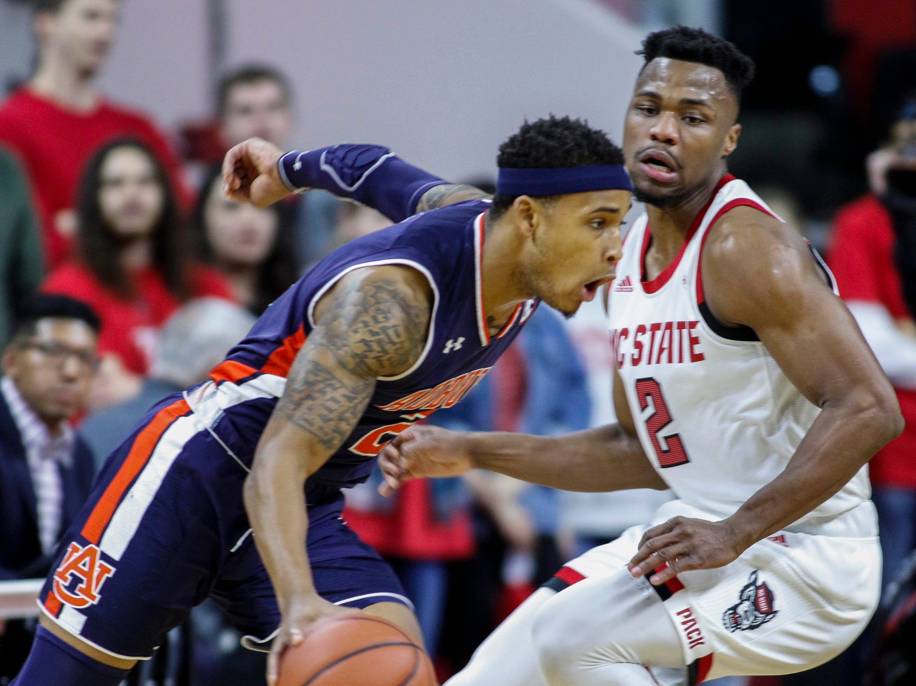 Dec 19, 2018; Raleigh, NC, USA; Auburn Tigers guard Bryce Brown (left) drives around North Carolina State Wolfpack guard Torin Dorn in the first half at PNC Arena. Mandatory Credit: Nell Redmond-USA TODAY Sports