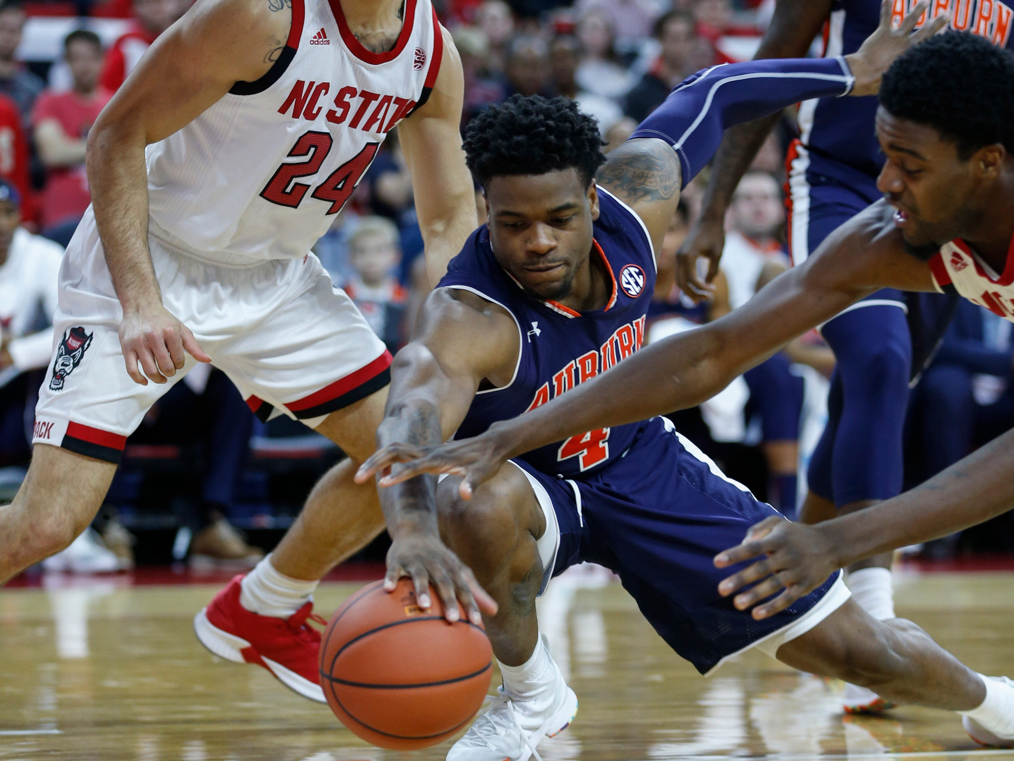Auburn guard Malik Dunbar (4) battles NC State forward DJ Funderburk (right) for a loose ball as guard Devon Daniels (24) looks on in the first half at PNC Arena on Dec. 19, 2018, in Raleigh, NC.