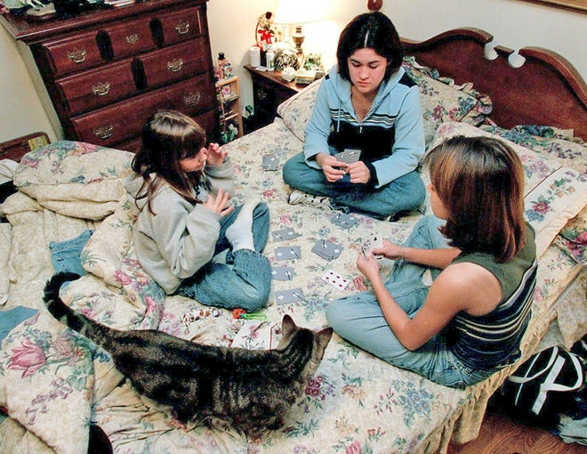 Sisters Tahliah, Tara and Tamera Cronk playing cards together in their temporary home in Fairview in 1999 after their mother's death.