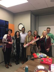 Community members join Zannie Martin (third from right) to wrap presents for families selected to receive gifts.