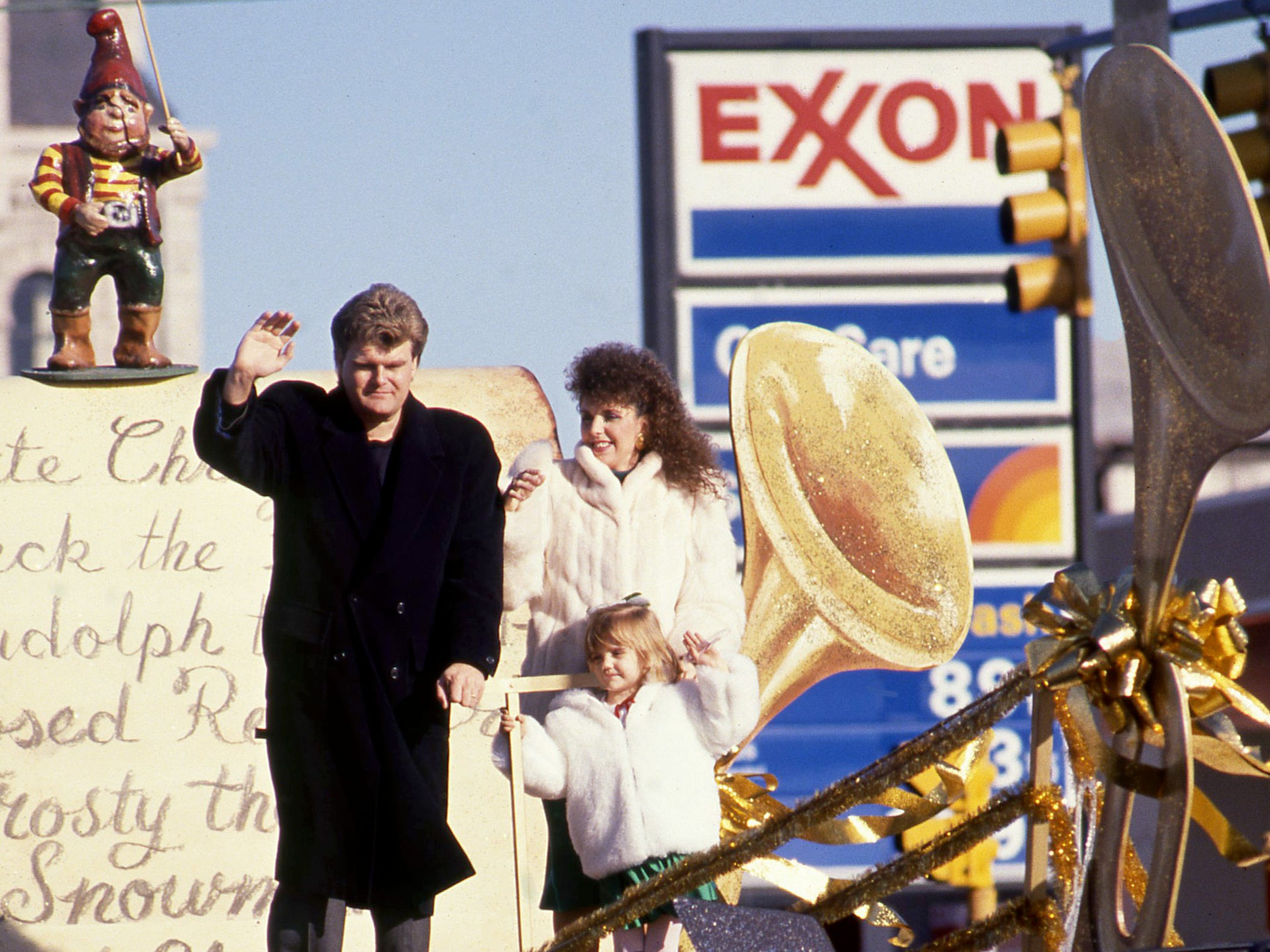 Grand marshals husband and wife country music stars Ricky Skaggs and Sharon White, along with their daughter, wave to the crowd during the annual Christmas parade Dec. 4, 1988.
