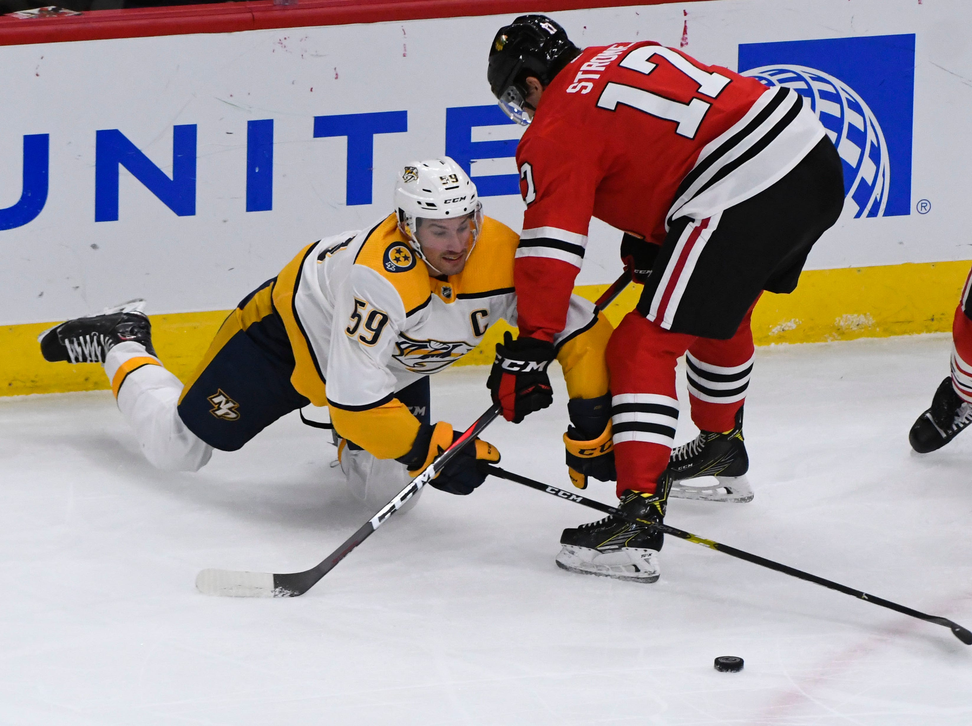 Dec 18, 2018; Chicago, IL, USA; Nashville Predators defenseman Roman Josi (59) and Chicago Blackhawks center Dylan Strome (17) fight for the puck during the first period at the United Center.